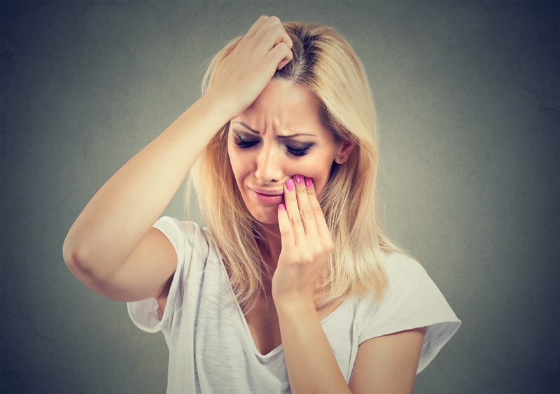 woman holding her face in pain