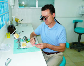 Dentist Dr. Richard Mitchell working in his office, on laboratory models