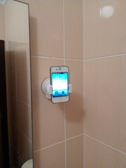 An iPhone in the Oral B Genius wall holder