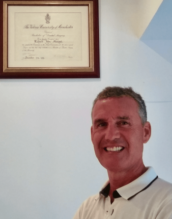 Dr. Richard Mitchell head and shoulders, with his dental degree in the background