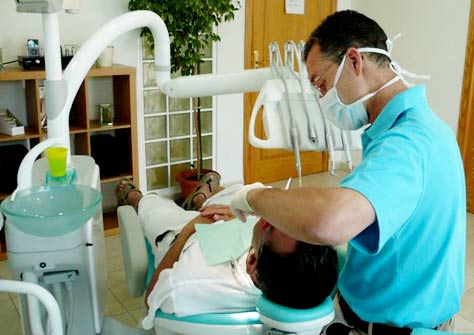 Dentist Dr. Richard Mitchell working in his office, wearing a facemask