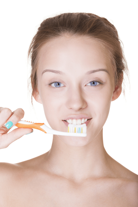 A young girl brushing her teeth, looking at the camera